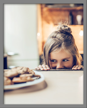 Young girl looking at plate of chocolate chip cookies mischievously